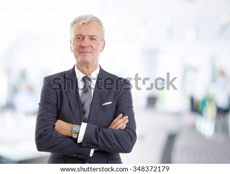 Portrait of executive financial director standing at office with arms crossed while looking at camera.  - stock photo