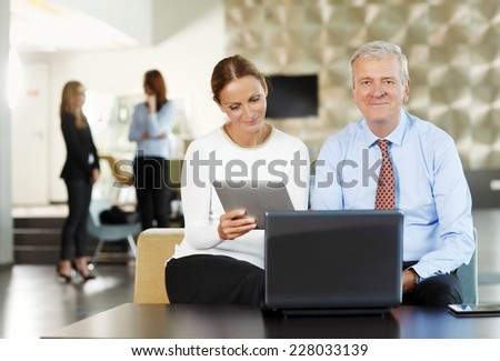 Portrait of executive old businessman working with business woman on laptop and digital tablet. Teamwork.  - stock photo
