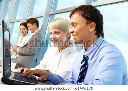 Portrait of executive partners looking at laptop display while working in office - stock photo