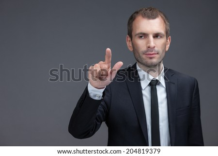 Portrait of executive pointing finger gestures, isolated on grey background. Concept of leadership and success - stock photo