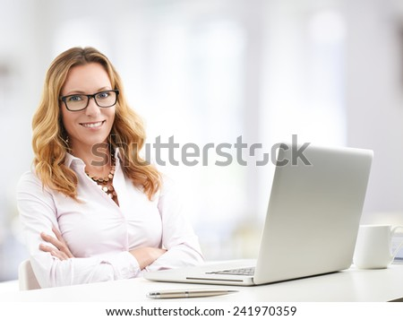 Portrait of executive sales woman working at laptop and calculating data while sitting at office.  - stock photo