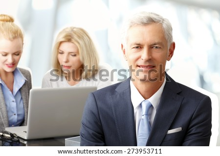 Portrait of executive senior businessman sitting at office and looking the camera. Busy sales women working on laptop at background.  - stock photo