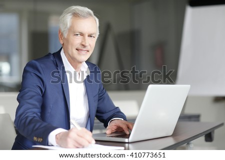 Portrait of executive senior director working on computer at his office. - stock photo