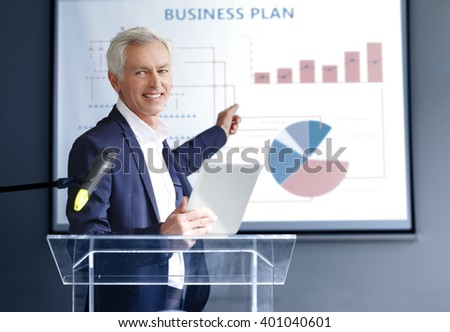 Portrait of executive senior professional businessman holding in his hand a digital tablet while giving a speech on seminar.
