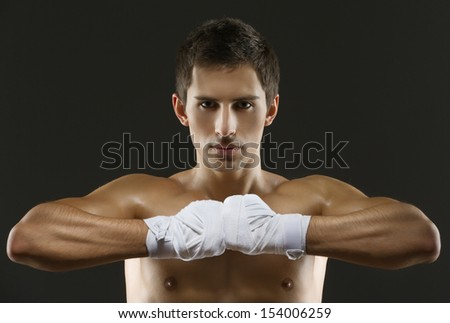Portrait of exercising boxer with hands wrapped with elastic bandage, isolated on black - stock photo