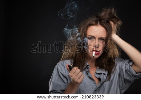 Portrait of exhausted female holding cigarette. bad looking woman smoking cigarette on black background - stock photo