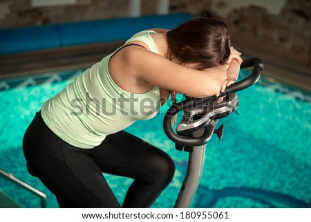 Portrait of exhausted woman spinning pedals on exercise bike - stock photo
