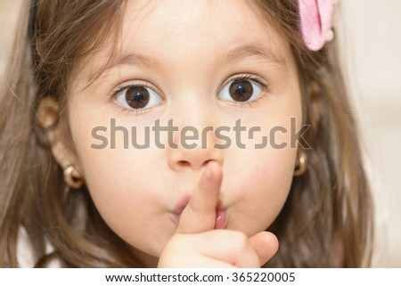 Portrait of expressive beautiful little girl finger up to lips for making a quiet gesture. Girl showing silence gesture looking at the camera - stock photo