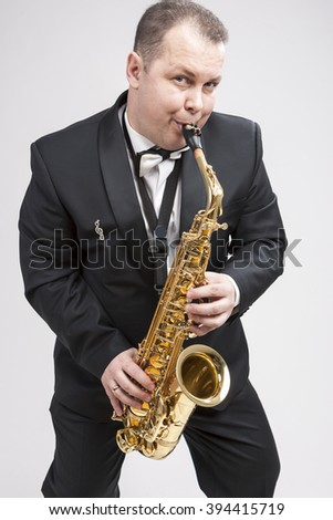 Portrait of Expressive Caucasian Player in Suit Playing on Saxophone.Vertical Composition - stock photo
