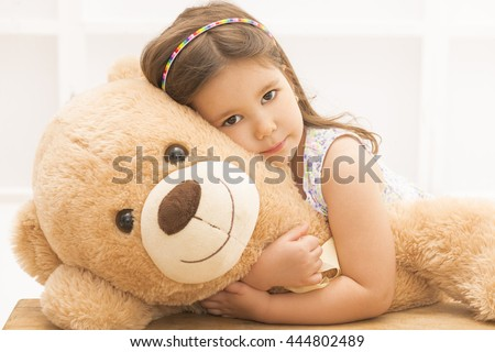 Portrait of expressive little girl hugging huge plush bear, indoor shot on white room. Little girl playing with teddy bear - stock photo