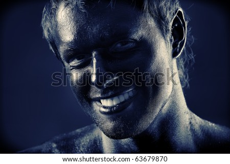 Portrait of expressive man painted with black color. Body painting project. - stock photo