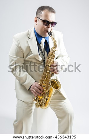 Portrait of Expressive Stylish Caucasian Saxophone Player Performing in White Suit and Sunglasses in Studio. Vertical Image Orientation