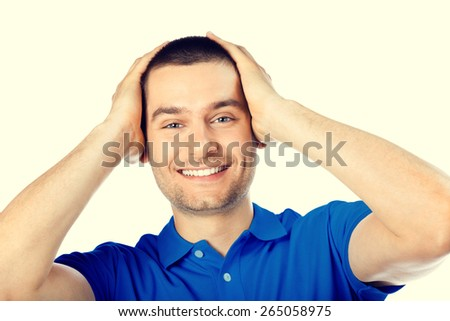Portrait of expressive surprised or shocked young attractive handsome man in blue casual t-shirt clothing, looking at camera - stock photo