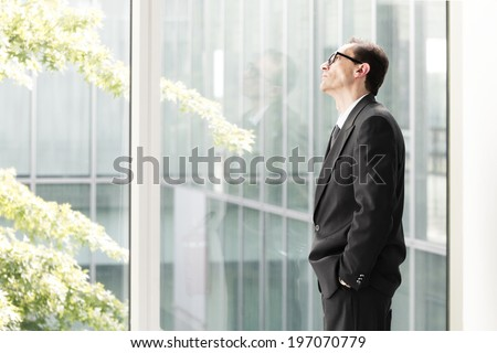 Portrait of Eyeglasses Daydreaming Businessman looking through the window - stock photo