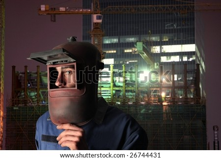 Portrait of factory welder on a cityscape background - stock photo