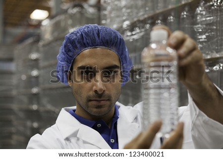 Portrait of factory worker holding water bottle - stock photo