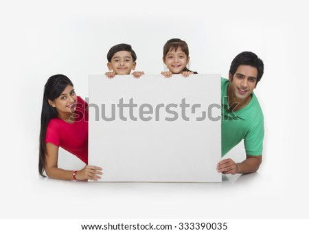 Portrait of family behind white board - stock photo