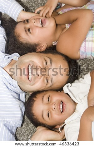 Portrait of family, dad playing his children at home - stock photo