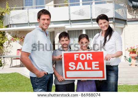 Portrait of family holding for sale sign standing outside their house - stock photo