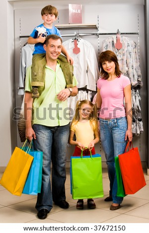 Portrait of family in clothing department of trade center - stock photo