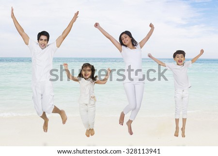 Portrait of family jumping in the air - stock photo