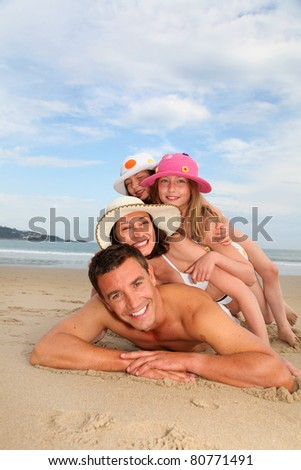 Portrait of family laying down sandy beach - stock photo