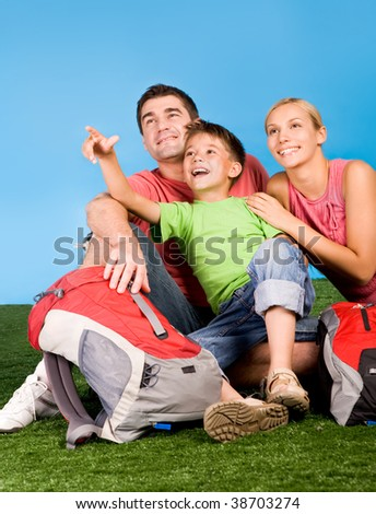 Portrait of family lying on grassland and looking where cute boy pointing during rest - stock photo