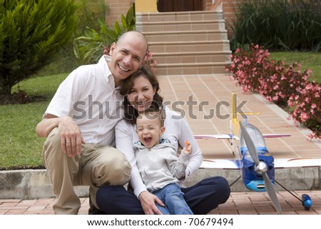 Portrait of family, mom and dad enjoying their son and airplane - stock photo