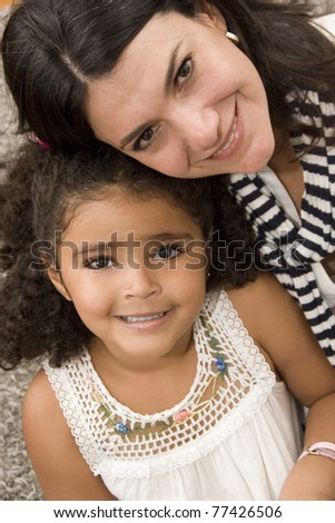 Portrait of family, mom playing with her beautiful daughter at home - stock photo