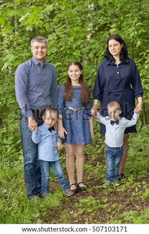 Portrait of family of five in green summer park.