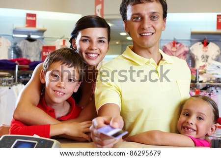 Portrait of family of four giving credit card - stock photo