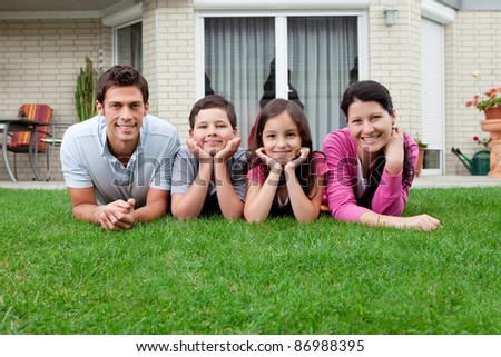 Portrait of family of four lying on lawn in their backyard - stock photo