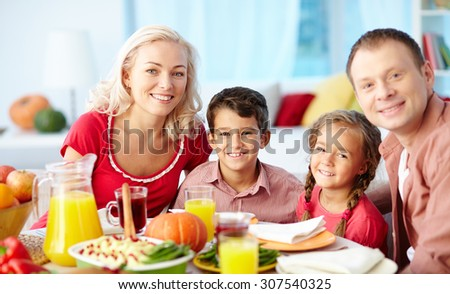 Portrait of family of four sitting at dining table - stock photo