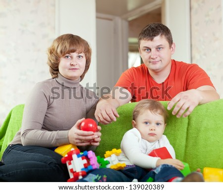 Portrait of family of three in home.  Focus on woman - stock photo