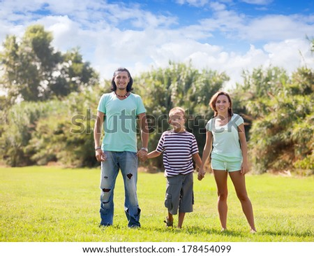 Portrait of  family of three in sunny summer park