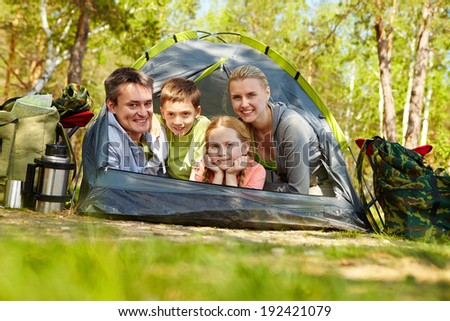 Portrait of family of travelers in tent looking at camera in the forest - stock photo