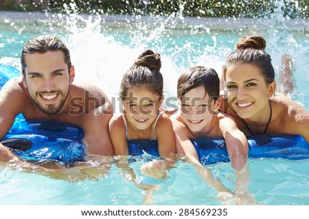 Portrait Of Family On Airbed In Swimming Pool - stock photo