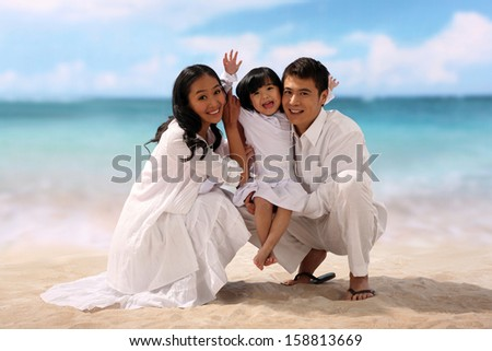 Portrait of family on beach - stock photo