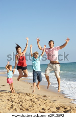 Portrait Of Family On Beach Holiday Jumping In Air - stock photo