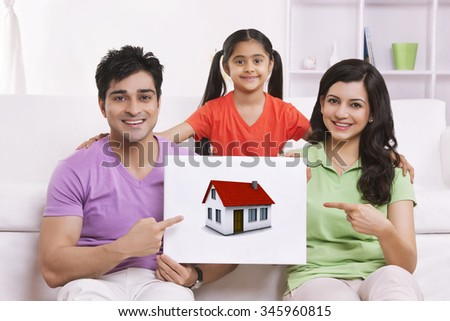Portrait of family pointing to picture of house