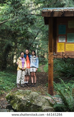 Portrait of family posing on hiking trail - stock photo