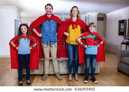 Portrait of family pretending to be superhero in living room at home - stock photo