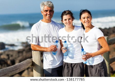 portrait of family relaxing after exercise at the beach - stock photo
