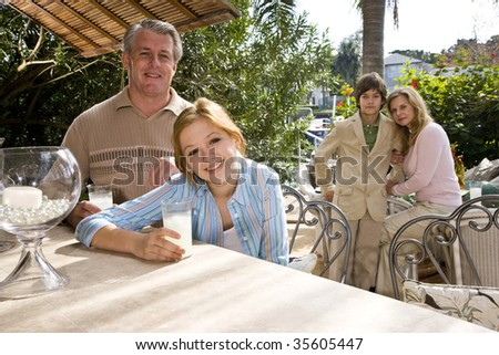 Portrait of family relaxing on outdoor patio - stock photo