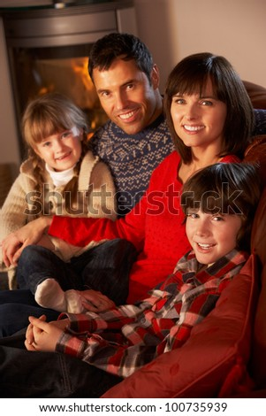 Portrait Of Family Relaxing On Sofa By Cosy Log Fire - stock photo