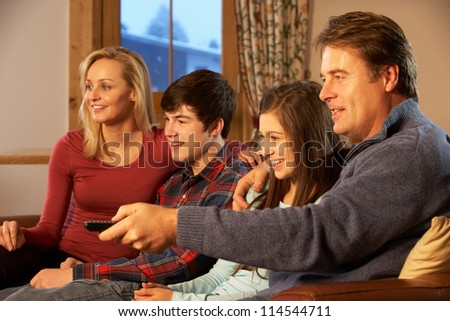 Portrait Of Family Relaxing On Sofa Together Watching TV