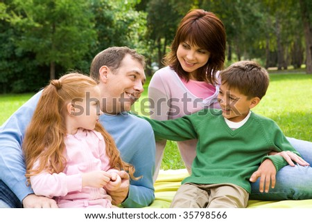 Portrait of family resting on the grass together - stock photo