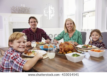Portrait Of Family Sitting Around Table Eating Meal At Home