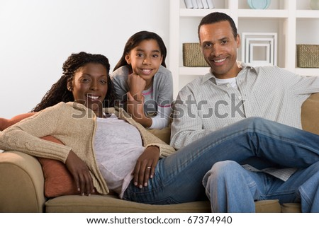 Portrait of family sitting on couch - stock photo