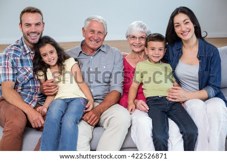 Portrait of family sitting on sofa and smiling in living room - stock photo